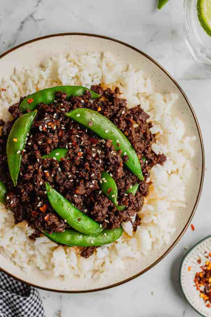 A plate filled with Spicy Korean-inspired Venison served on top of rice. It is garnished with snap peas, sesame seeds, and red pepper flakes.