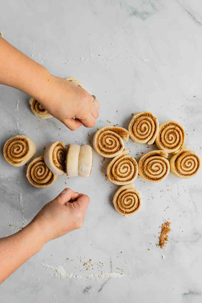 Two hands use a piece of dental floss to cut cinnamon rolls into even pieces.