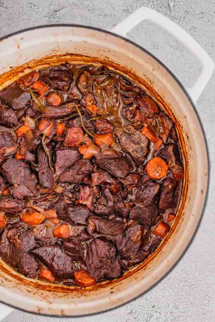 A white dutch oven filled with perfectly cooked red wine venison stew.
