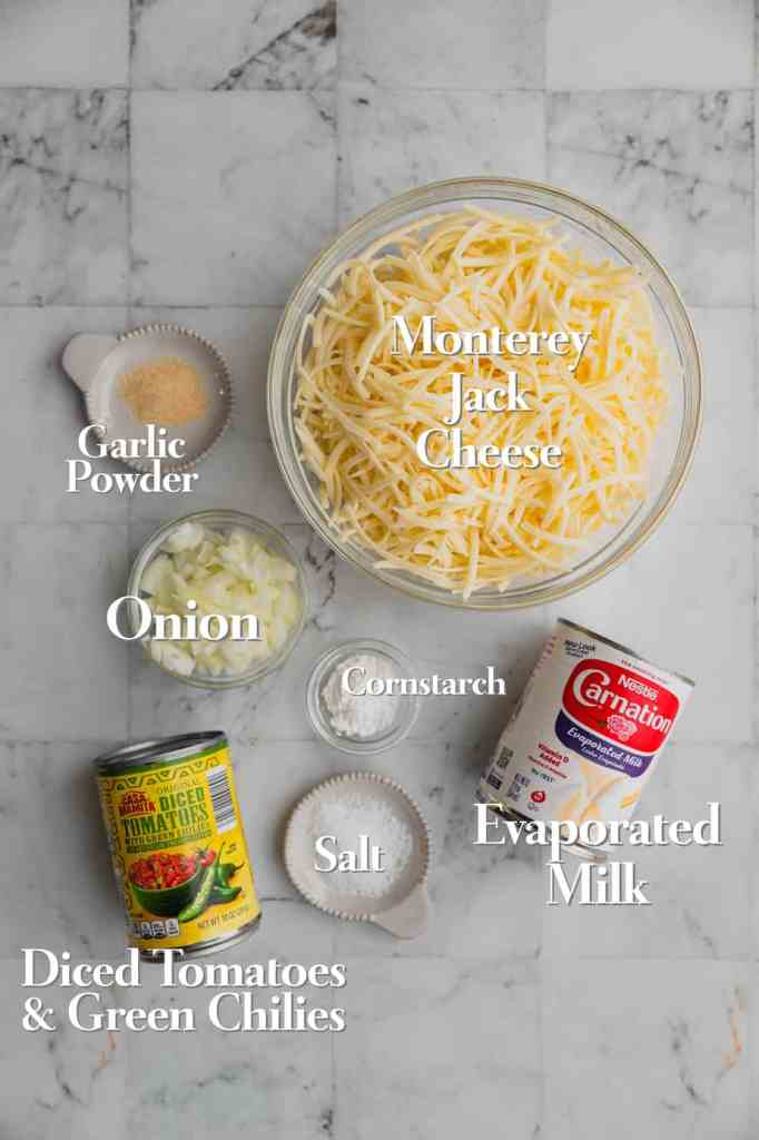 All of the ingredients for homemade white cheese queso are on a marble backdrop.