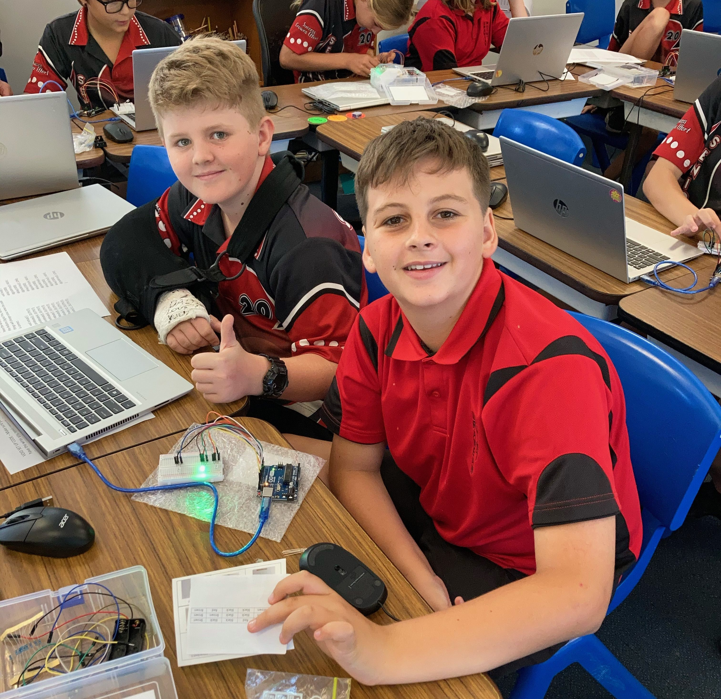 Two students with a laptop and an electronics project. Both smile at the camera and one gives a thumbs up