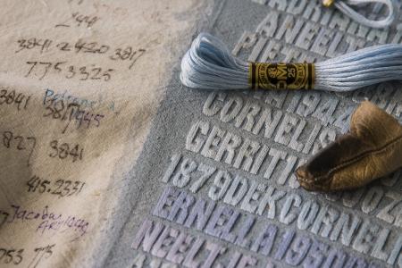 De Verdronkenen (2003-2008). Detail van het werk in wording. met een lederen vingerhoedje, de DMC-garens en aantekeningen van de kunstenares op de rand van het doek.Vijf panelen met de namen van alle 1836 slachtoffers van de Watersnoodramp van 1 februari 1953. Monumentaal werk van Miep van Riessen in acryl en garens op doek - 134 x 236,8 cm. Stichting Miep van Riessen foto © Jan van de Ven  4288x2848 pixels