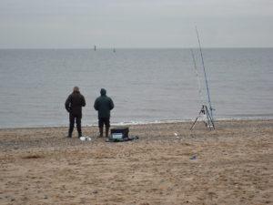 deux pêcheurs tentent de pêcher au bord de l'eau
