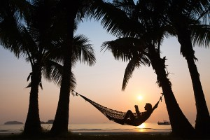 Summer reading list for entrepreneurs - Image: man in a hammock in a tropical scene