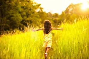 little girl running through high grass