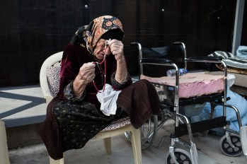 A displaced Christian woman prays inside the Saint Joseph Church in Erbil, Iraqi Kurdistan, Aug. 28, 2014. The church gives refuge to thousands of Christians that were displaced by the advance of the terrorist group calling itself the Islamic State. Thousands of internally displaced people fled to Erbil from neighboring provinces. On June 5, 2014, the Islamic State of Iraq or ISIS and aligned forces began a major offensive in northern Iraq with the Iraqi Government. This conflict led many Iraqis to flee their homes in search of Safety. Caritas Iraq and CRS have been supporting these internally displaced civilians. Photo by Daniel Etter for Catholic Relief Services
