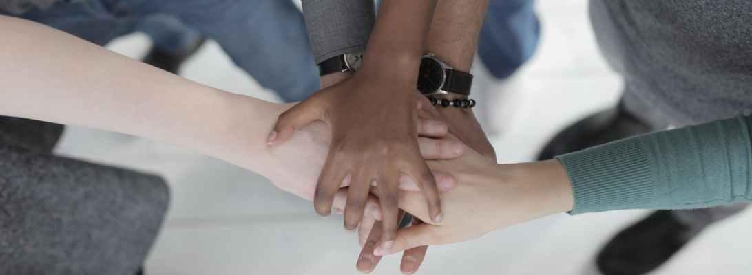 crop unrecognizable multiethnic colleagues joining hands