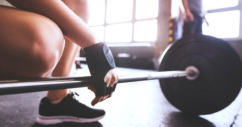 Close-up of woman preparing to lift barbell in gym