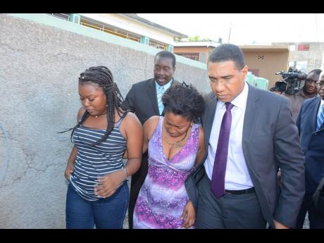 Prime Minister Andrew Holness and National Security Minister Robert Montague on Monday visited Bryden Street in east Kingston to meet the relatives of slain Woman Corporal Judith Williams. (Jamaica Star picture)