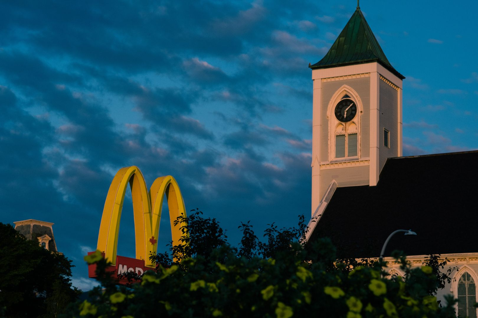 A photo depicting Mcdonalds Sign and Church Morning Light