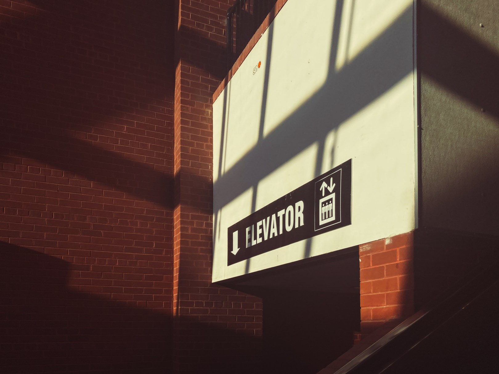 A photo of elevator sign in shadows