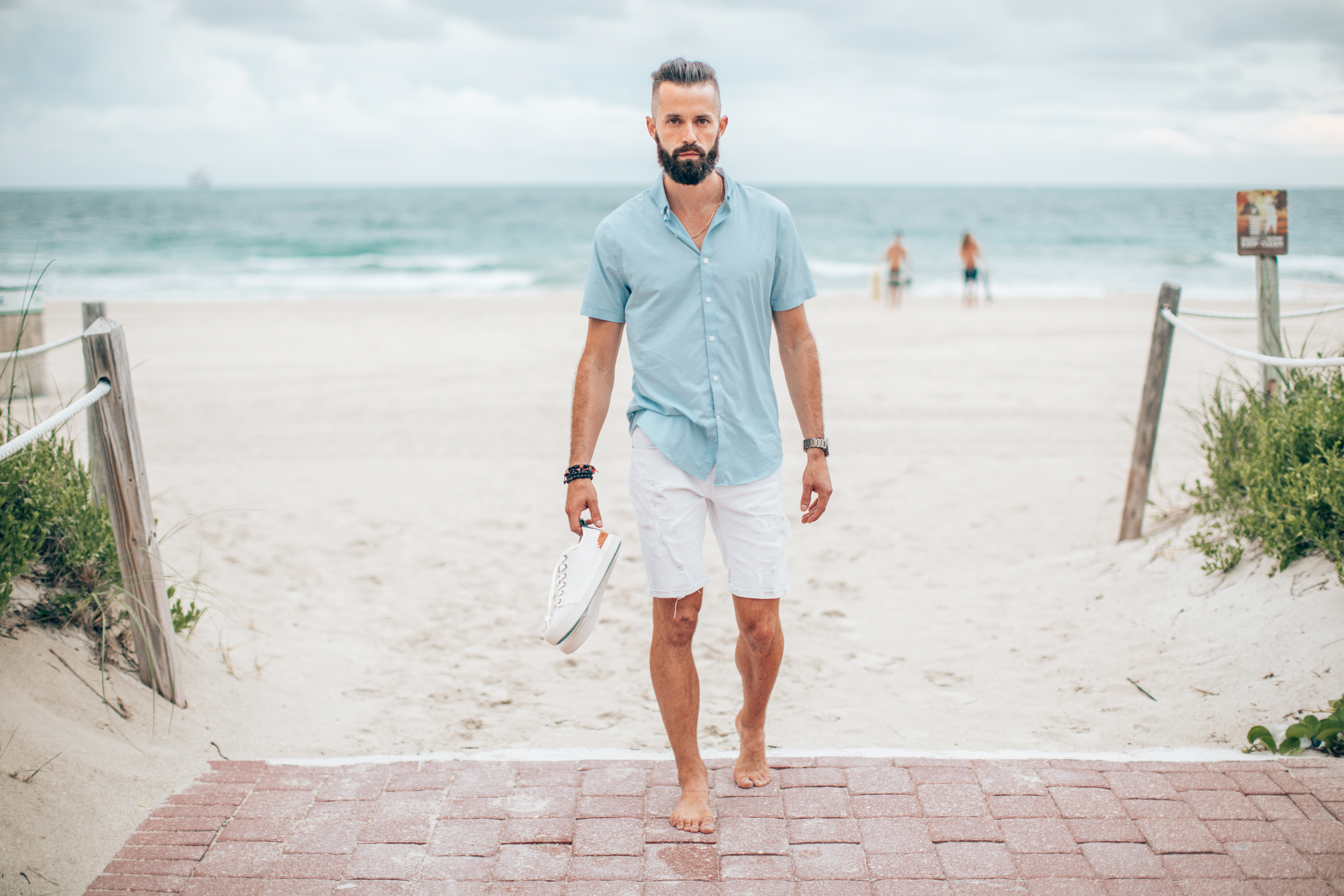 Michael Checkers summer street style fashion photo in South Beach Miami holding shoes on the beach walking foward