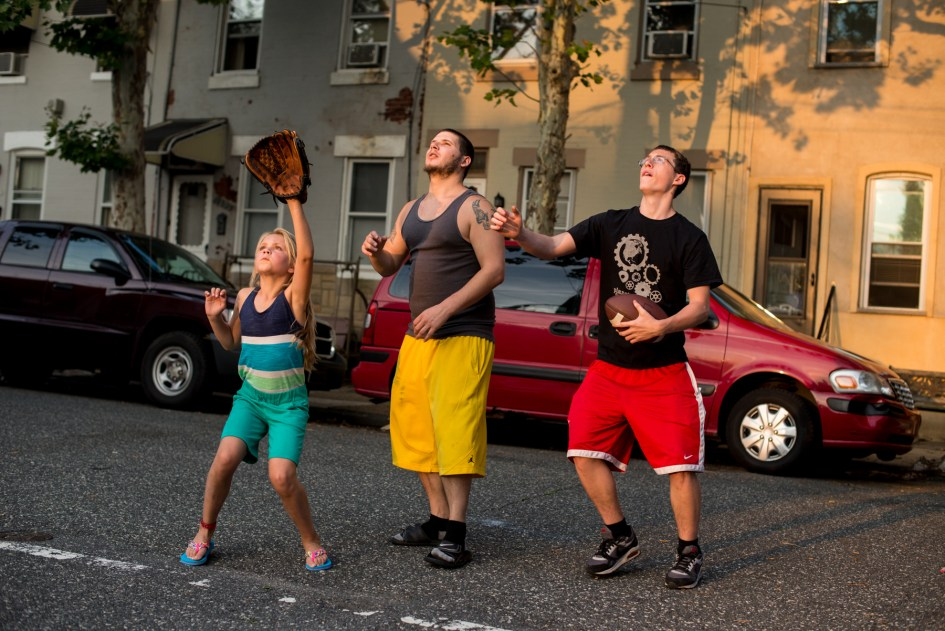 Philadelphia, PA - July 1, 2015 - Older guys playing with younger kids in the neighborhood. Forgotten Bottom.