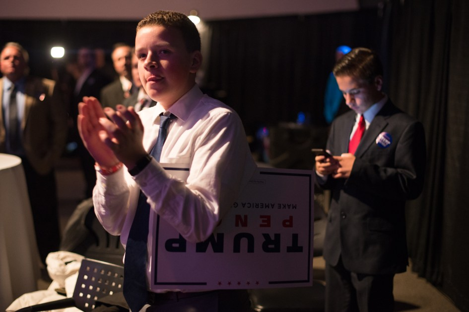 Braintree, MA – Nov. 8, 2016 – Cody Christman, left, 14, of Lowell, Massachusetts, reacts as United States presidential election results are reported on Fox News during the Massachusetts Trump-Pence Campaign victory party. Trump supporters gathered at the F1 Boston race track to cheer on their nominee as he was elected 45th president of the United States.