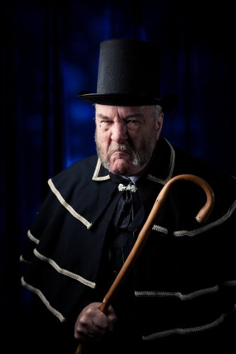 old man ebenezer scrooge looks grouchy with cane