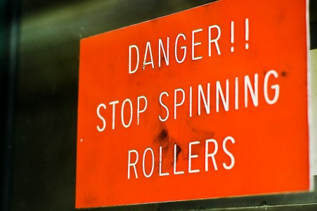 This sign is found on the second level of the former press and warns pressman not to paper rollers while moving.