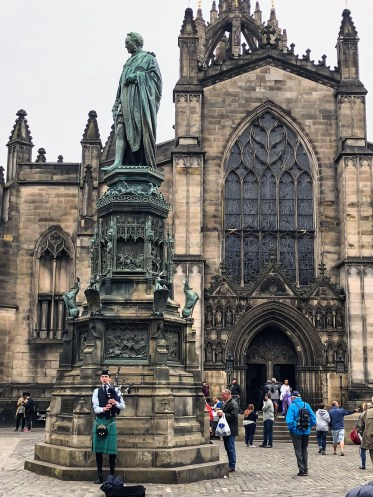 A bagpiper plays in front of St. Giles Cathederal on the Royal Mile in Edinburgh, Scotland.