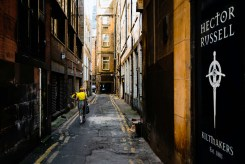 The woman in yellow with her yellow flowers, walks down a dingy, beat up alleyway off the Buchannan Street pedesrian mall in Glasgow, Scotland.