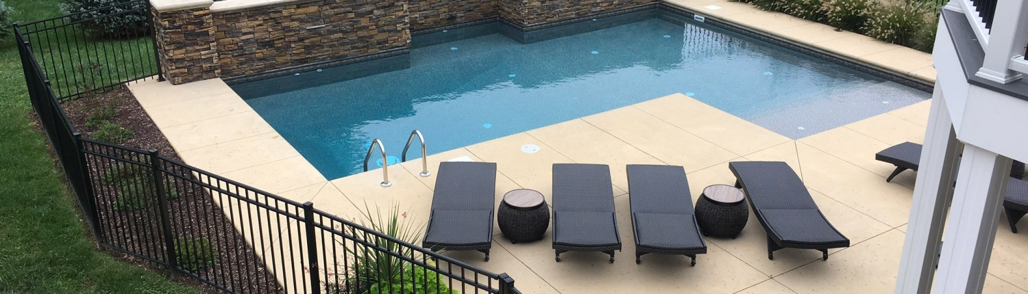 New Pool Installation with Concrete Deck and Stone Wall Feature
