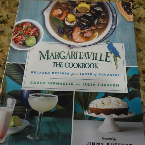 The cover of the new cookbook Margaritaville The Cookbook. On the cover is a bowl of pico de gallo a bowl of seafood stew a margarita in a salt-rimmed glass and some sort of frosted cake