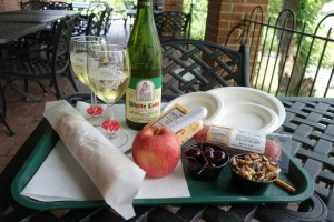 A lunch plate at the Hermannhof Winery. Twos glasses of white wine a loaf of bread wrapped in white patper an apple, cheese , bowl of black cherries and a bowl of black walnuts.