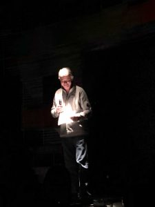 Mike Pound on the stage at The Second City TV. The stage is black and Mike is standing under a spot light.