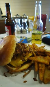 A photo of a bacon cheeseburger with farmer fries and two bottle of beers in the background