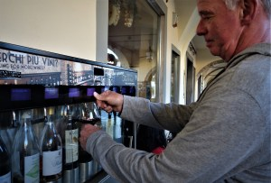 MIke Pound getting wine out of a wine vending machine while in Italy.