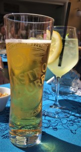 a picture of a tall class of beer sitting next to some sort of wine spritzer with a slice of lemon in the glass.