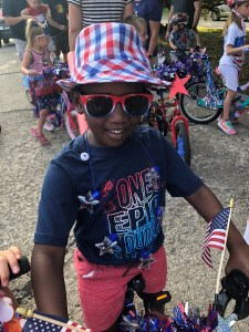 picture of a young boy on his bike before the parade. He is wearing a blue patriotic shirt, red shorts and a red, white and blue, fedora along with red framed sunglasses.