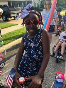 a girl on her bike before the parade. Wearing a red white and blue stared dress.