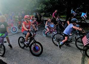 a tight shut of the begining of the race. A kid in a red shirt with a red helment riding a bike surrounded by other kids on their bikes