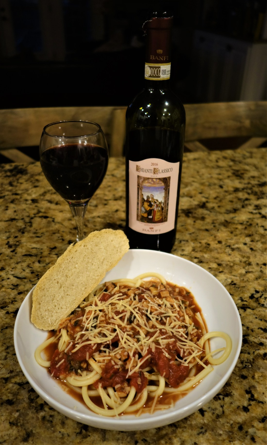 a bow of pasta with clam sauce, with a slice of Italian bread on the edge of the bowl. Behind the bowl is a glass of Chianti sitting next to a bottle of Chianti.