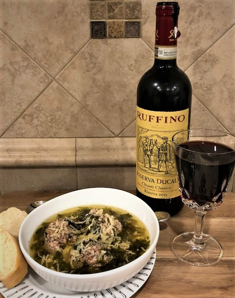 A picture of a bowl of Italian Wedding soup on a plate with two pieces of sliced Italian bread on the side Next to the plate and bowl is glass of Chianti sitting next to an opened bottle of Chianti.