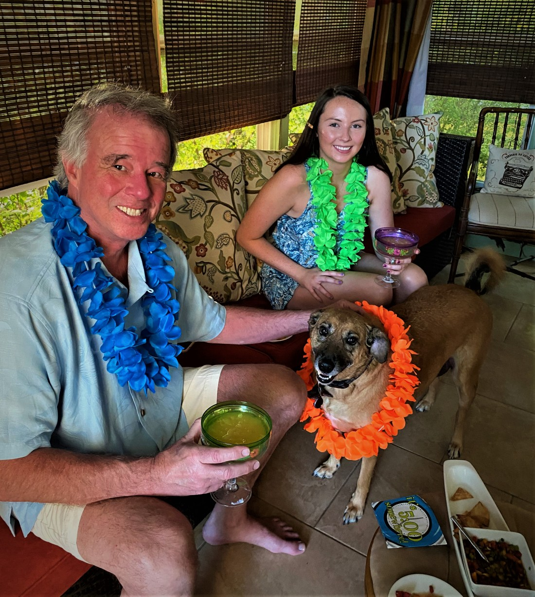 Mike Pound sitting on the couch on the three season porch. Sitting next to him is his daughter Emma and between them is their dog Caicos. Mike, Emma and Caicos are wearing leis.