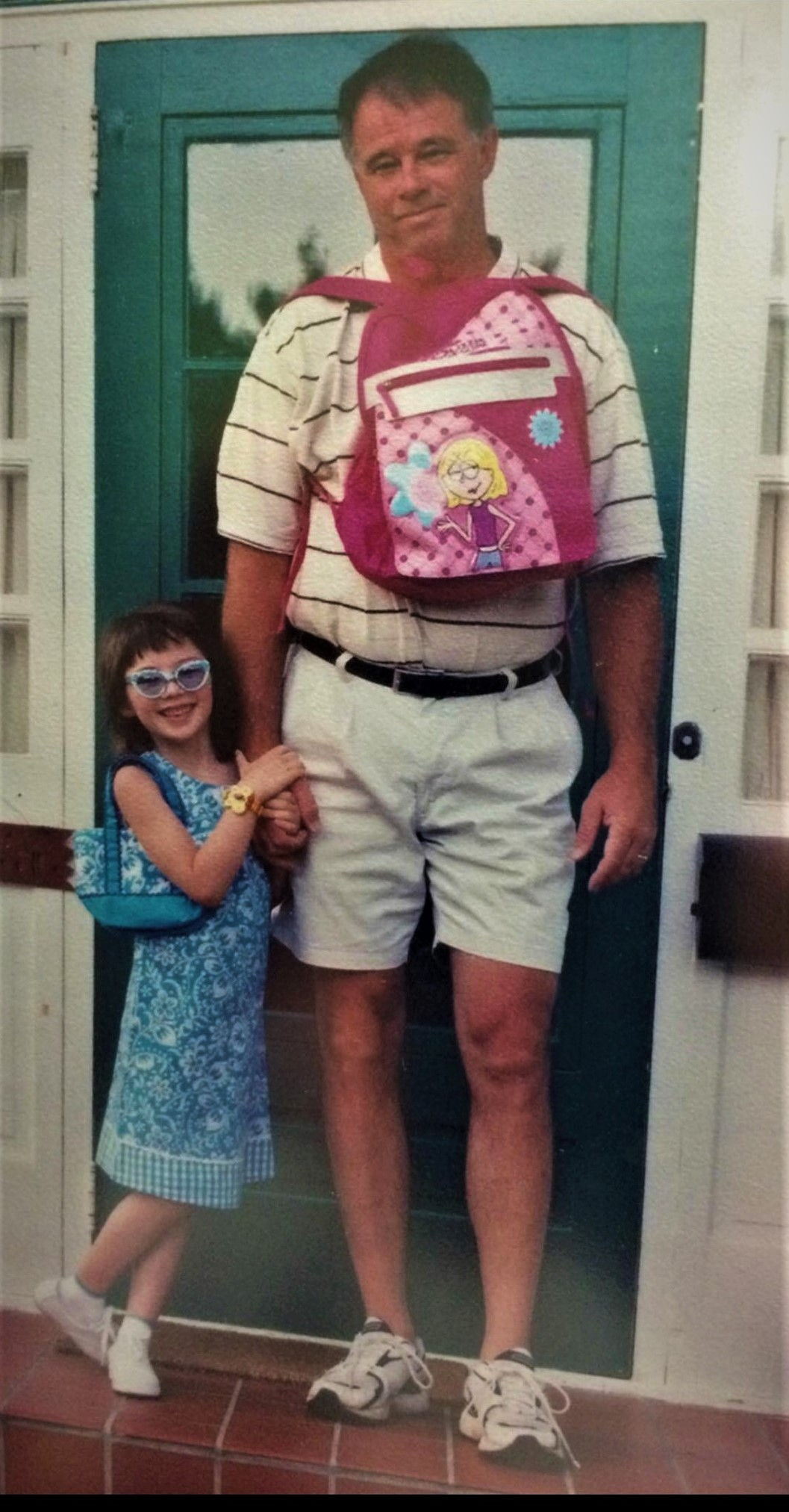 a picture of mike and emma on her first day of kindergarten. Emma on the left is about waist high to mike and is hold his hand. She is wearing sunglasses and a new watch. Mike has Emma's backpack on his chest.