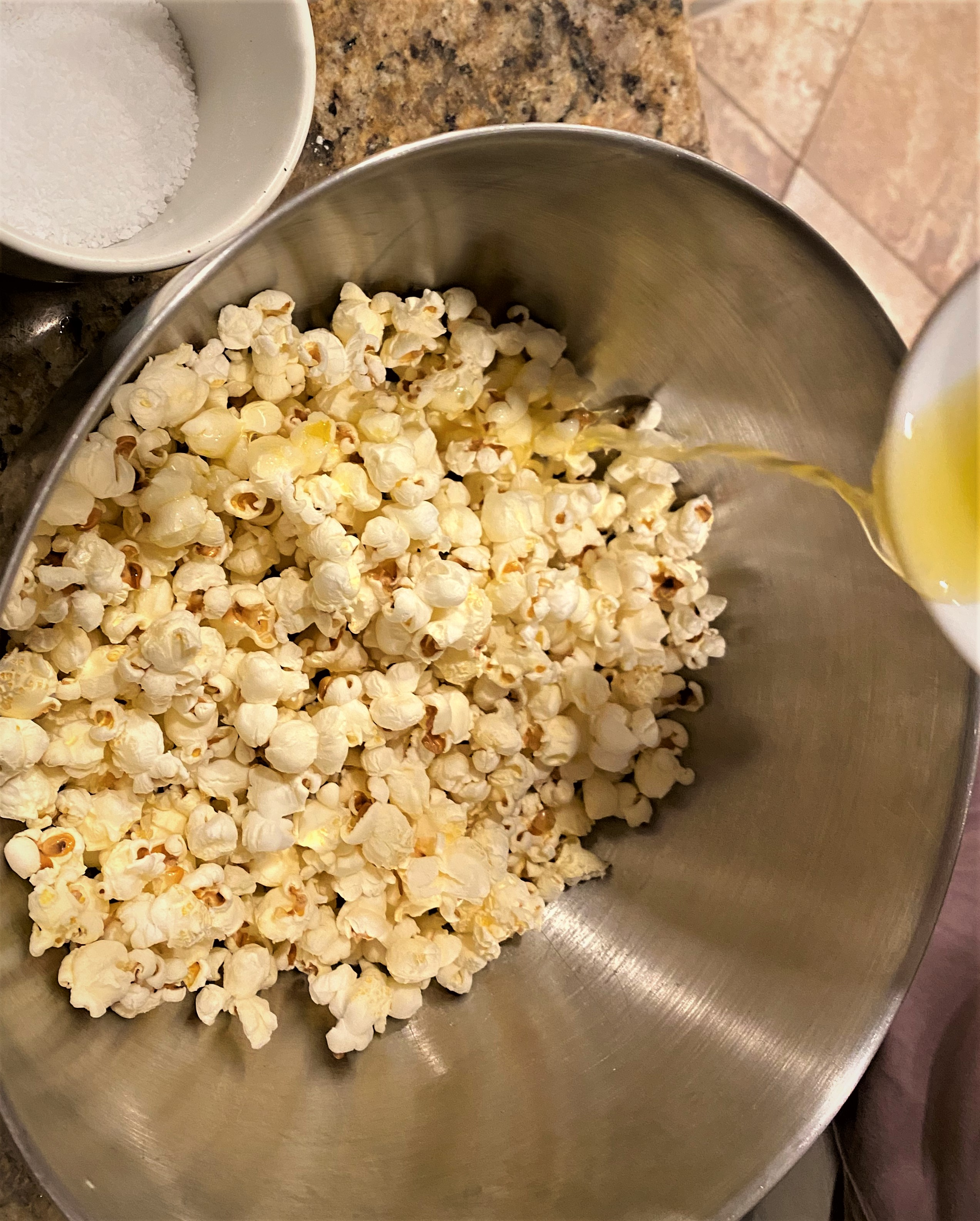 A bowl about 1/3 full of popcorn with butter being poured on top.