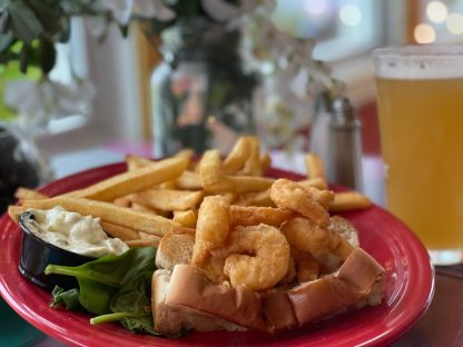 Crispy battered shrimp in a grilled roll with fries and tartar on the side