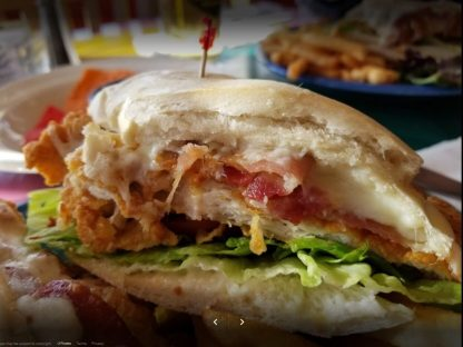 crispy chicken sandwich on a french roll with cheese and bacon