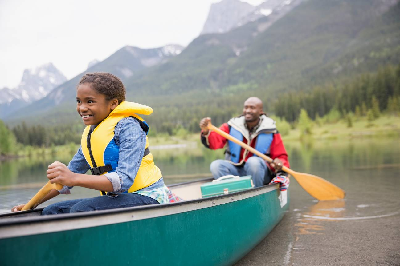 Daughter and Father boating on a mountain lake