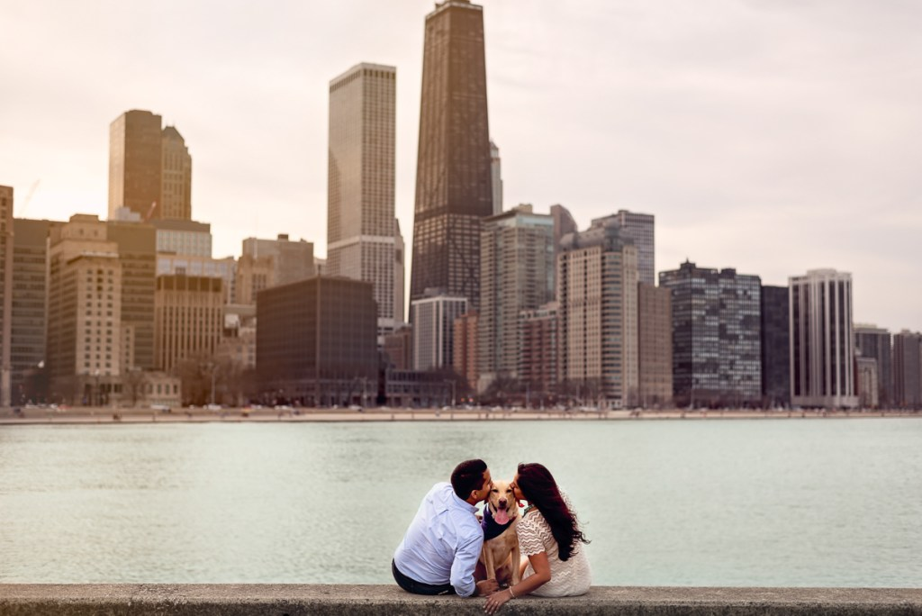 An engagement session for an engaged couple and a dog kissing at Olive Park in Chicago in the fall by a wedding photographer Mila Craila Photography