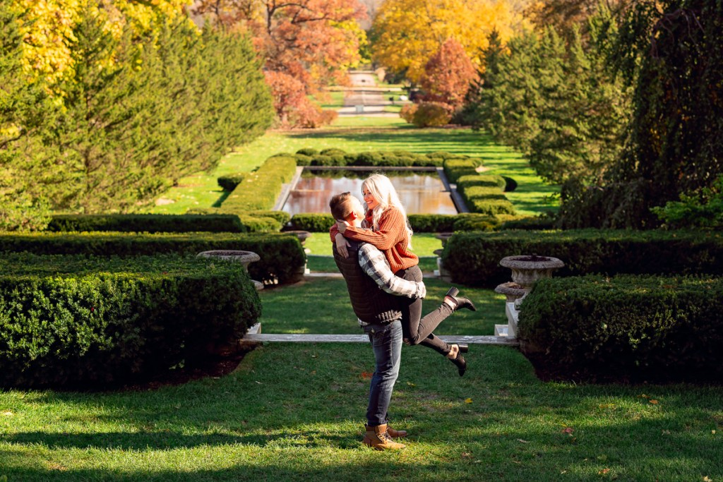 An engagement session for an engaged couple kissing at Cantigny Park in Wheaton in the fall by a wedding photographer Mila Craila Photography