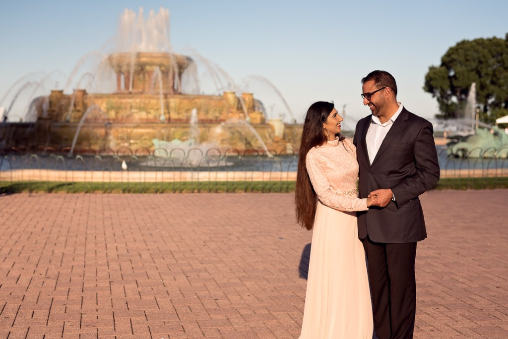 An engagement session for an engaged couple at the Buckingham Fountain in Chicago in the summer by a wedding photographer Mila Craila Photography