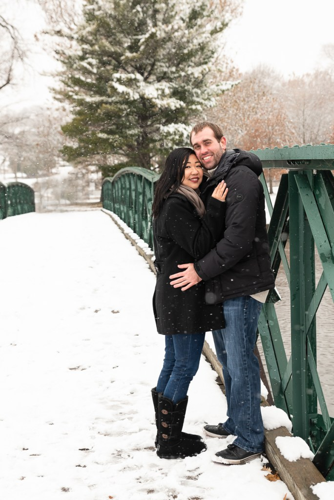 An engagement session for an engaged couple standing on a bridge at Fabyan Forest Preserve in the winter by a wedding photographer Mila Craila Photography