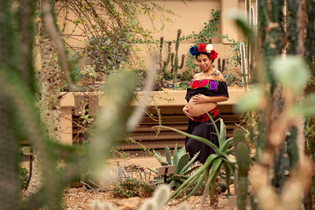 A maternity session for a pregnant woman in a traditional Mexican dress in desert of Garfield Park Conservatory by a maternity photographer Mila Craila Photography