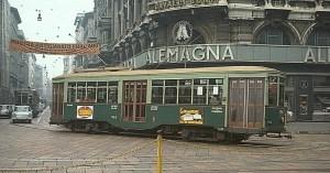Milano degli anni '70: i tram sferragliano davanti alle vetrine dei marchi della grande distribuzione di allora.