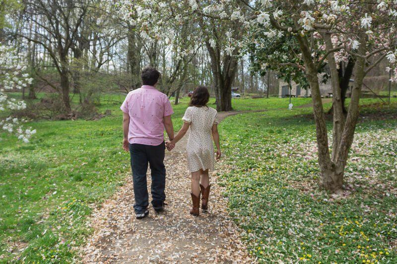 Man and woman holding hands walking on path in Wissahickon Park Philadelphia