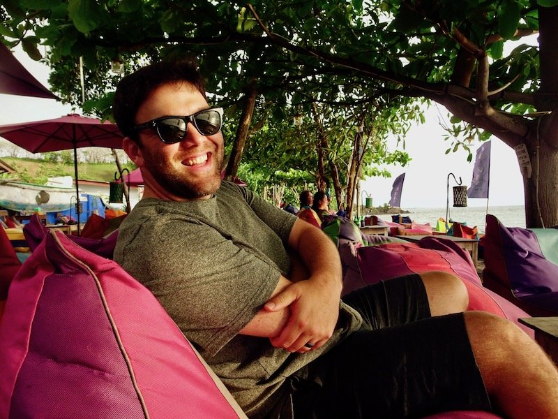 Man sitting on pink chair on beach with sunglasses on