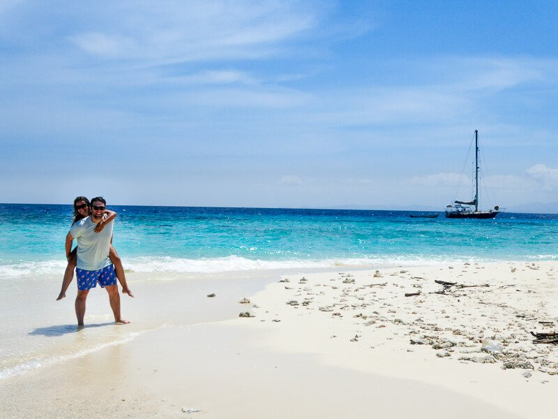 Couple on white sand beach in Pacific sailboat on the water behind them Fiji