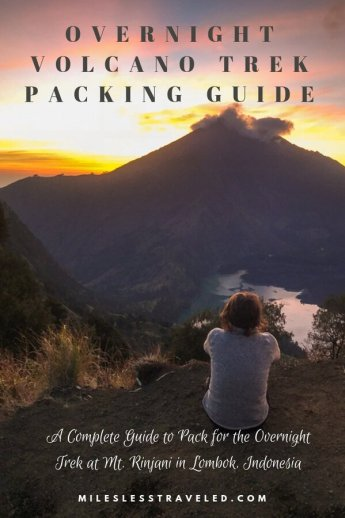 Woman sitting with back to camera watching sunrise over peak of Mt Rinjani in Indonesia Text Overlay Overnight Volcano Trek Packing Guide